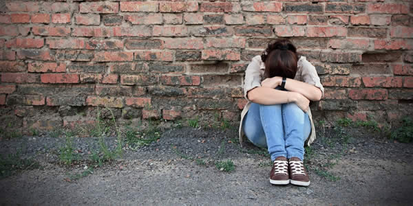Young woman in despair sitting against a brick wall