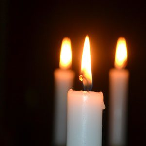 three lit candles in a dark room