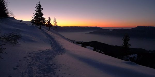 the sun rising over a snow covered medow