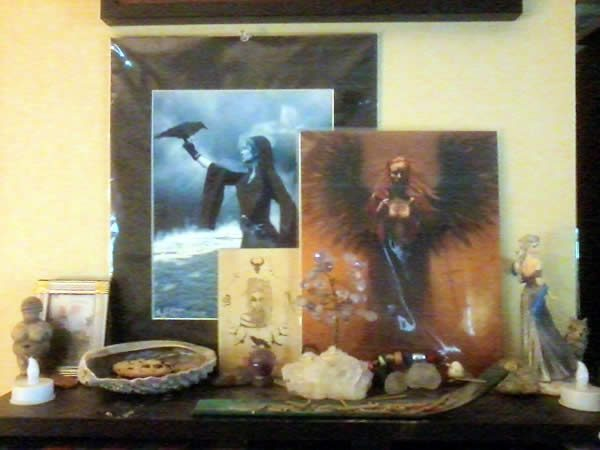 a table top shrine with art prints, stones, and other paraphrenalia.