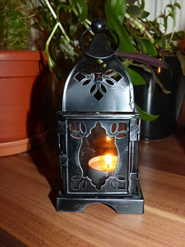 a lantern with a lit tea light candel within it
