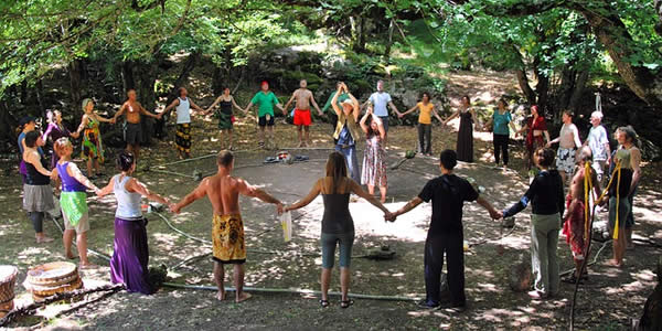 a group of people in a circle holding hands as two more people stand in the center speaking to them