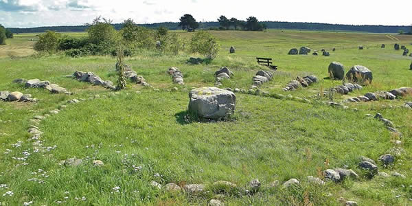 a stone circle with a center altar on a green hilltop