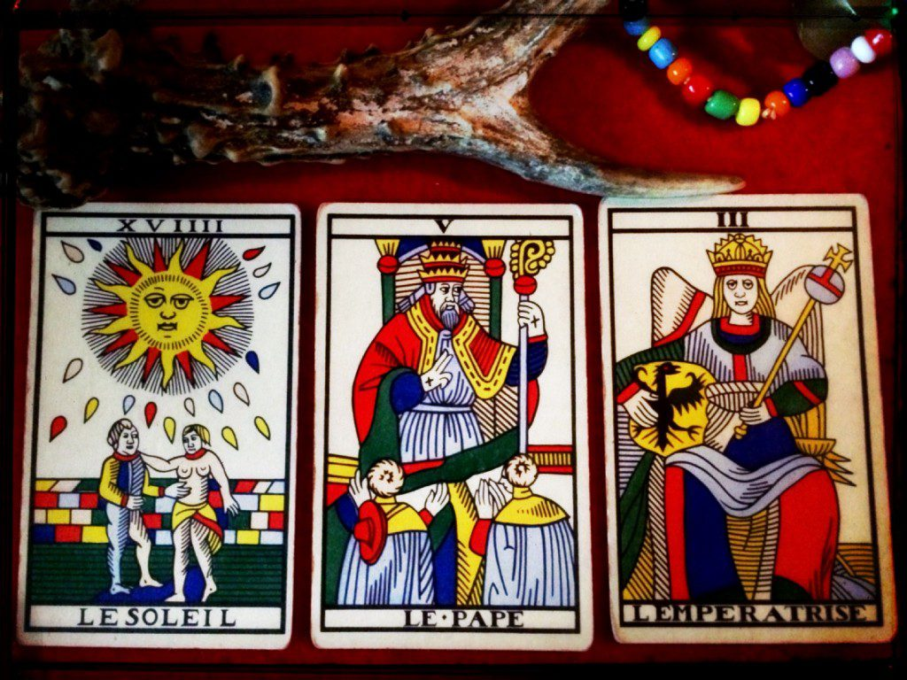 three tarot cards -- the sun, the pope, and the empress -- on a red table cloth