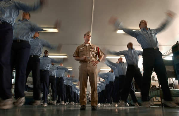 a drill instructor and a room full of cadets doing jumping jacks