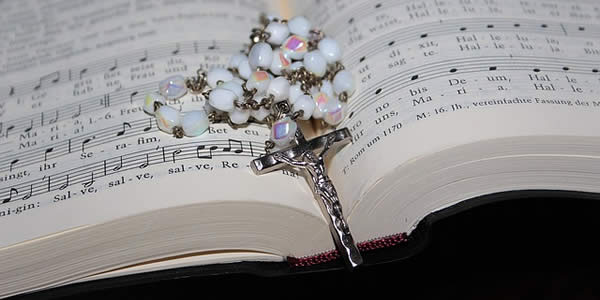an open hymnal with a rosary on top of it