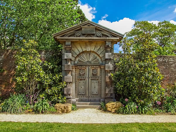 an ornate, human-sized stone door in a garden