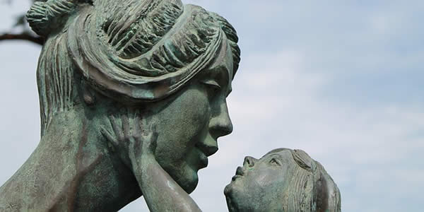a statue of a mother with her infant child reaching up to touch her face
