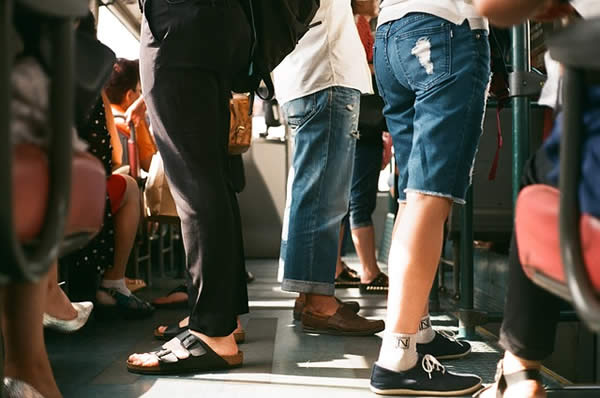 the legs of those standing to ride on a subway car