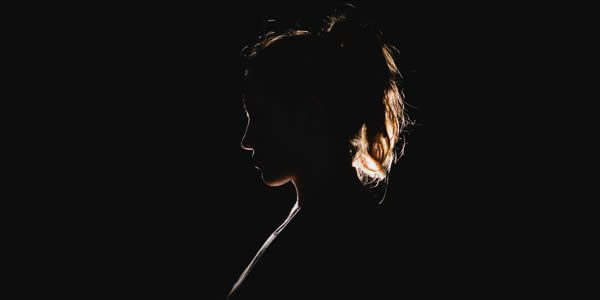 a backlit woman in a dark room