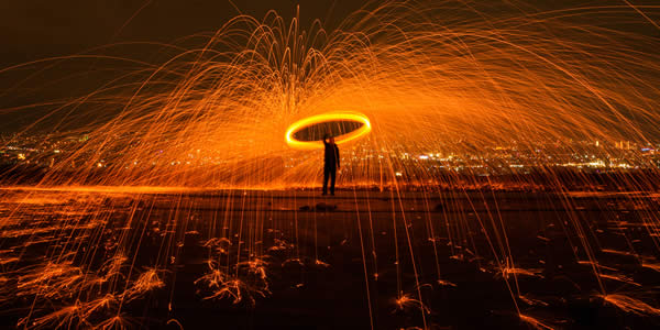 a man spinning a burning object creating a ring of fire and sparks shooting from it