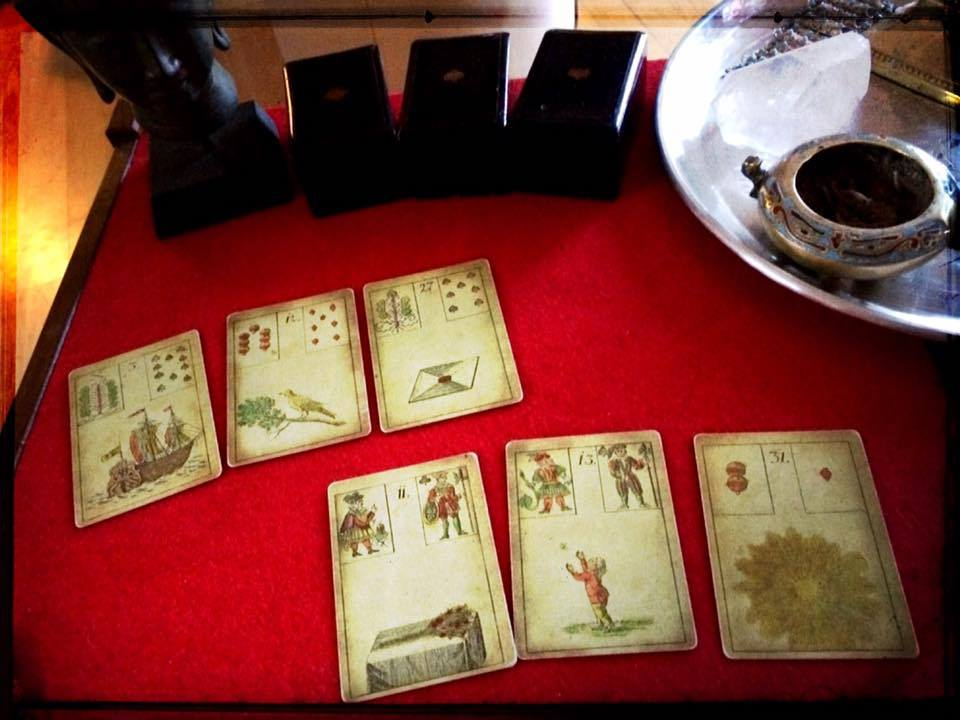 six tarot cards on a red table cloth