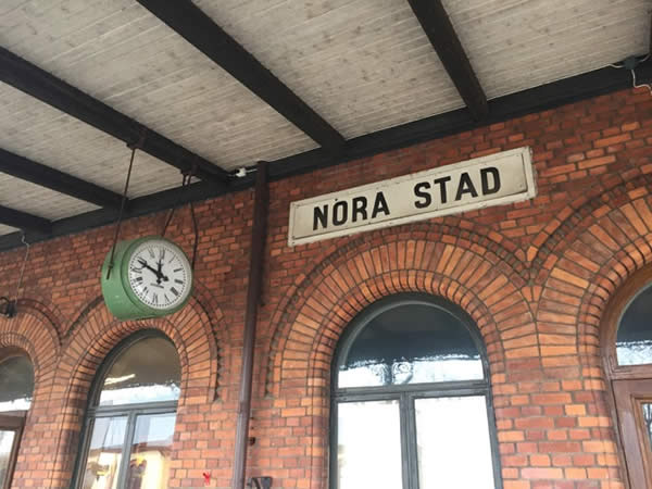 """a brick building showing an exterior clock with the Swedish phrase """"Nora Stad"""" (translation: Nora Station)"""