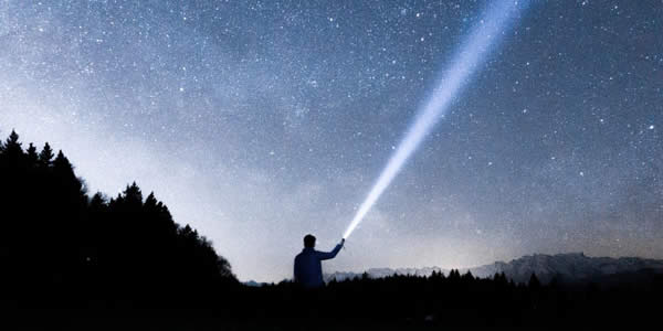 a man at night pointing a lit flashlight to the sky