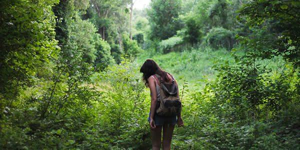 a woman walking in a overgrown field