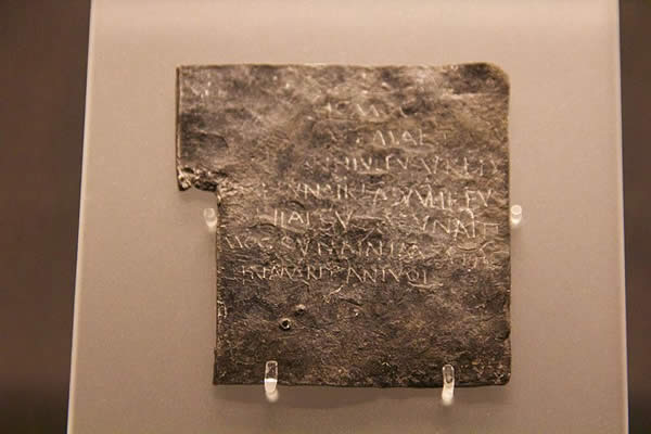 a stone tablet with a Latin enscription on display in a museum