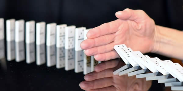 a hand blocking the fall of a line of dominoes