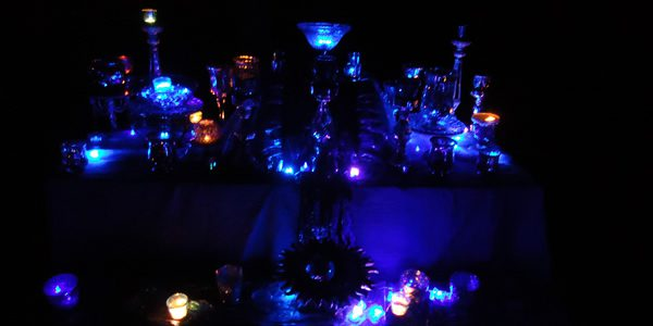 an altar illuminated by small candles in an otherwise dark room