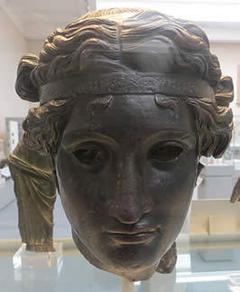 a bronze mask of a young man