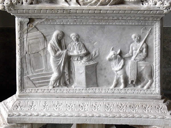 a marble relief depicting three people sacrificing a cow or bull
