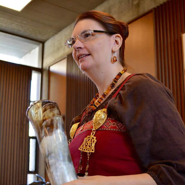 a woman, the author, holds a drinking horn
