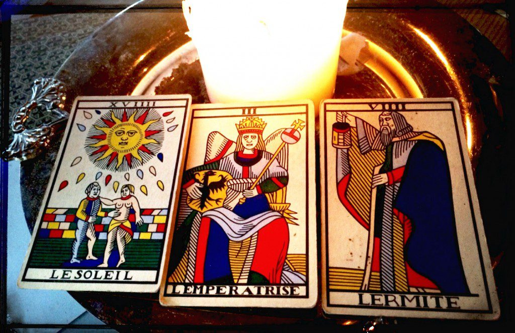 a spread of three tarot cards: the sun, the emperor, and the hermit