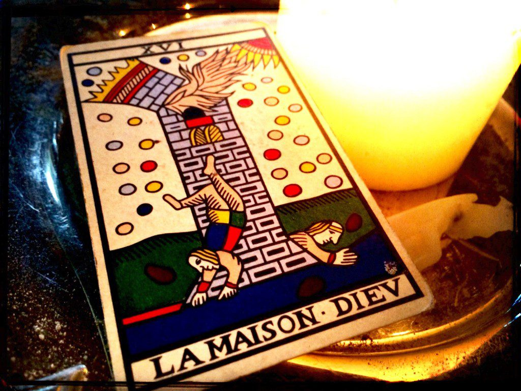 a tarot card, the Tower, next to a lit candle
