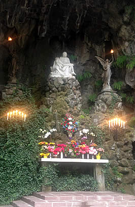a statue in a shallow cave with an altar of flowers before it
