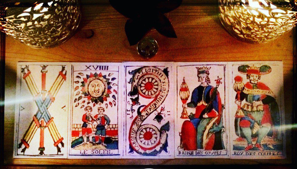 five tarot cards arranged on a table side to side