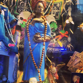 a statue of a woman in a blue dress adorned with a rosary