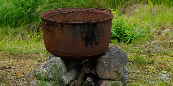 a cauldron placed outside on a firepit