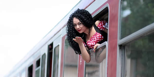 a woman leans out the window of a train and blows a kiss
