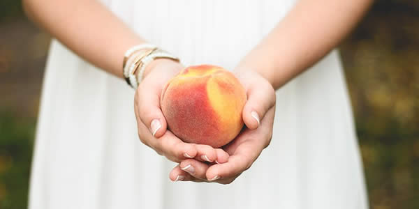 a woman holding a peach in both hands