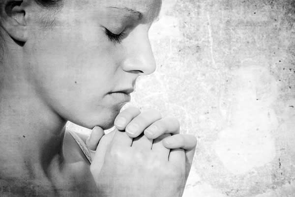 a woman clasping her hands before her in prayer