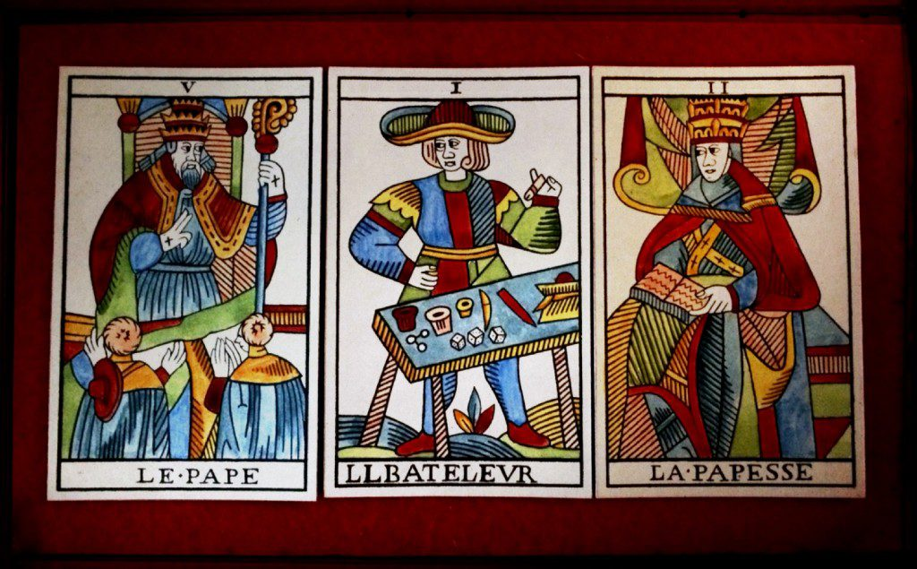 three tarot cards -- The Pope, The Magician, The Popess - face up on a field of red