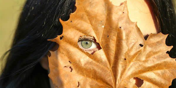 a woman peeking out through a whole in an autumn leaf