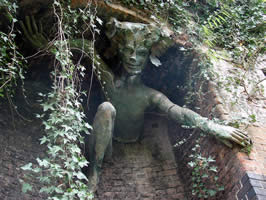 a humanoid figure crawling from a hidden space in a wall
