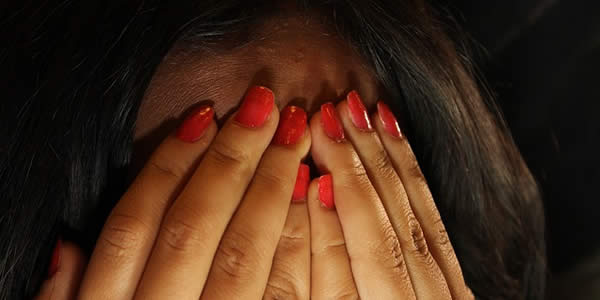 a woman holding her hands over her face