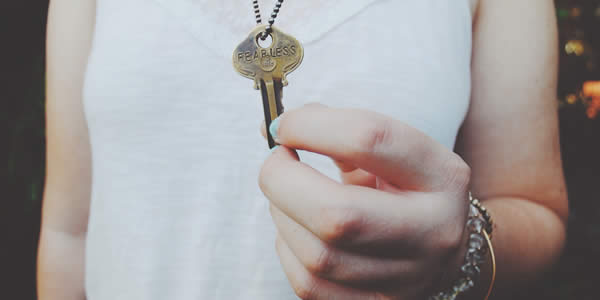 """a woman holds a key hung aruond her neck; on the key the word """"fearless"""" has been stamped"""