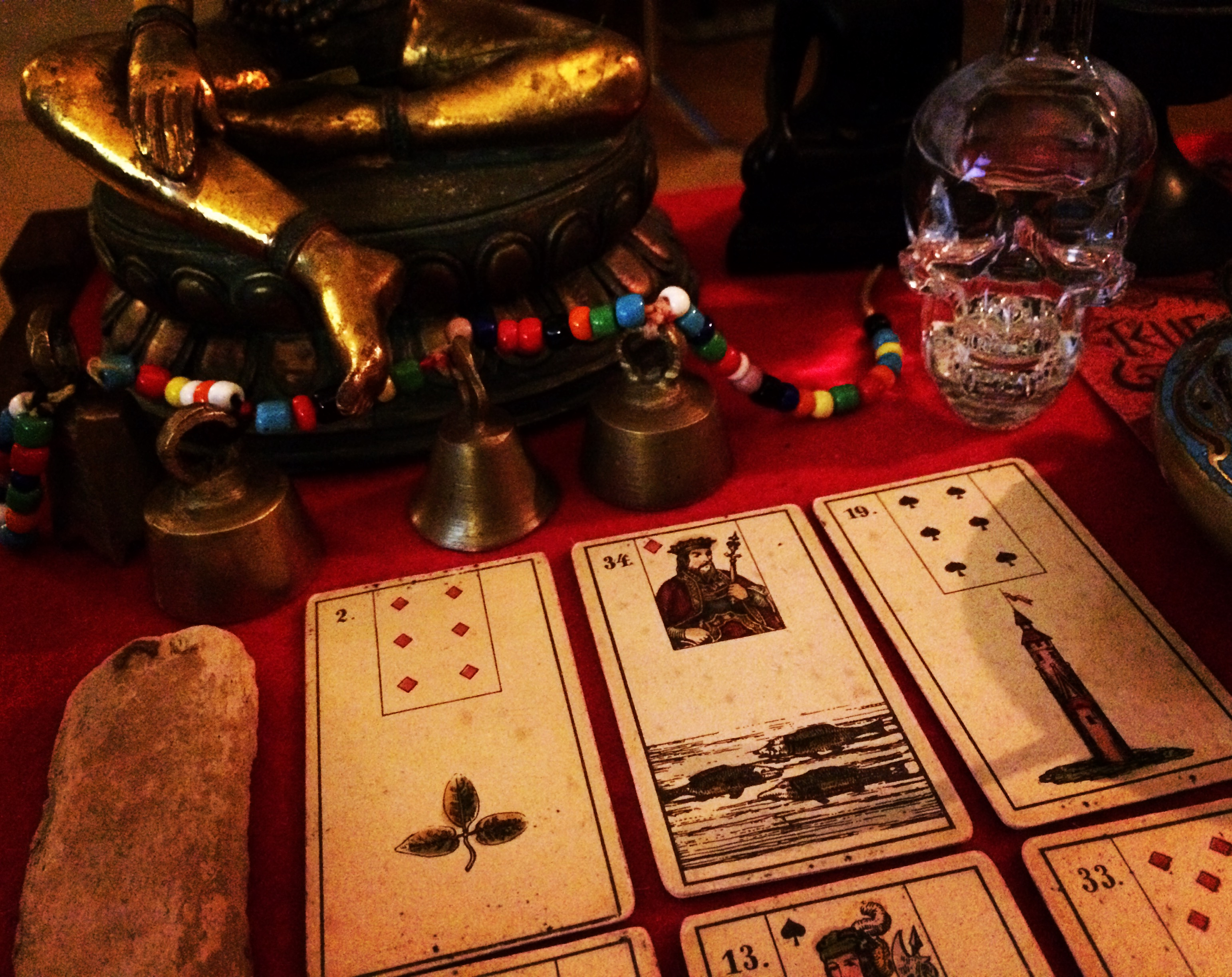 cards in a three by three grid next to a crystal skull, beads, and bells