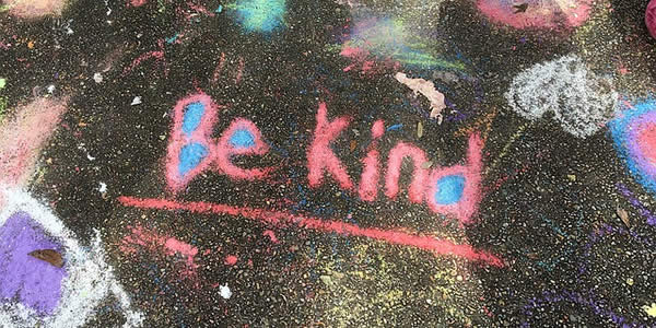 "the words ""be kind"" written in colorful chalk on a sidewalk"