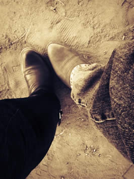a photograph taken while looking down the subject's leg at their cowboy boots
