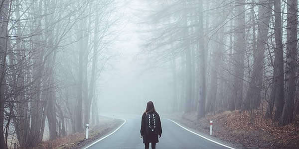 a woman standing in the middle of a road facing away from the camera looking into a fog bank