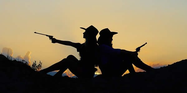 two women sillohuetted by the setting sun holding pistols