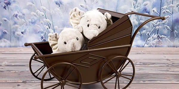 a pair of plush elephant dolls in a baby stroller