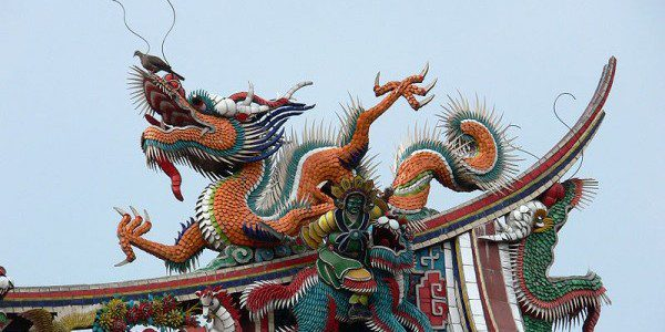 a dragon sculpture on the roof of a building