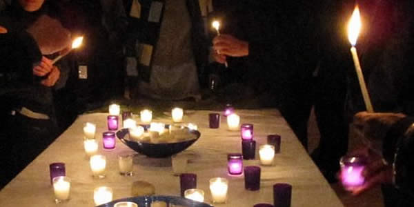 Lighting candles at a past year's Longest Night service (Picture the Homeless).