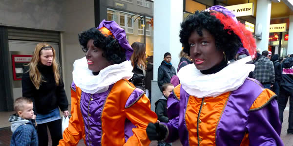 two women in black face wearing purple and orange costumes