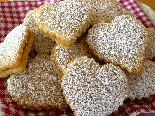 heart-shaped, sugar-dusted cookies arranged on a plate