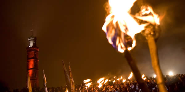 a crowd gathers at beltane with torches
